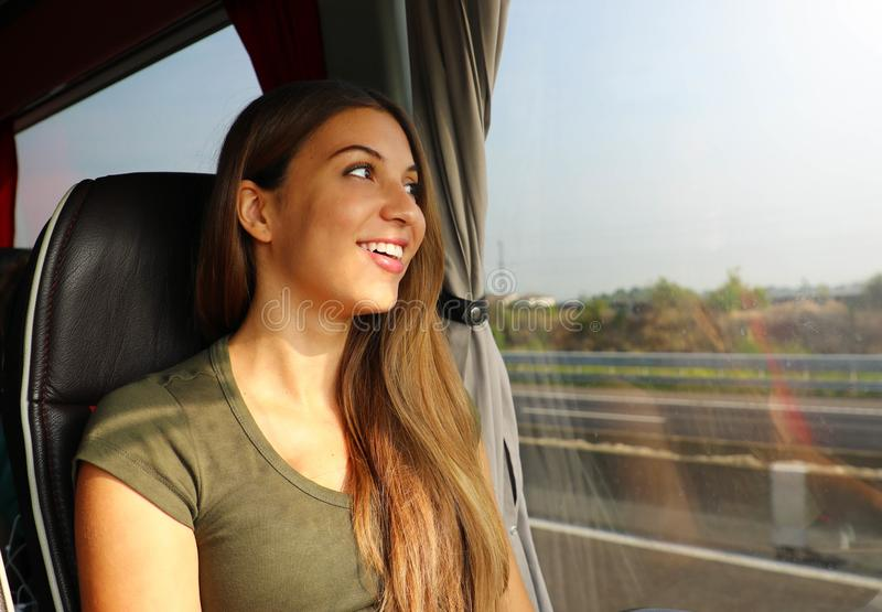 Young beautiful woman looking through the bus window. Happy bus passenger traveling sitting in a seat and looking through the royalty free stock images