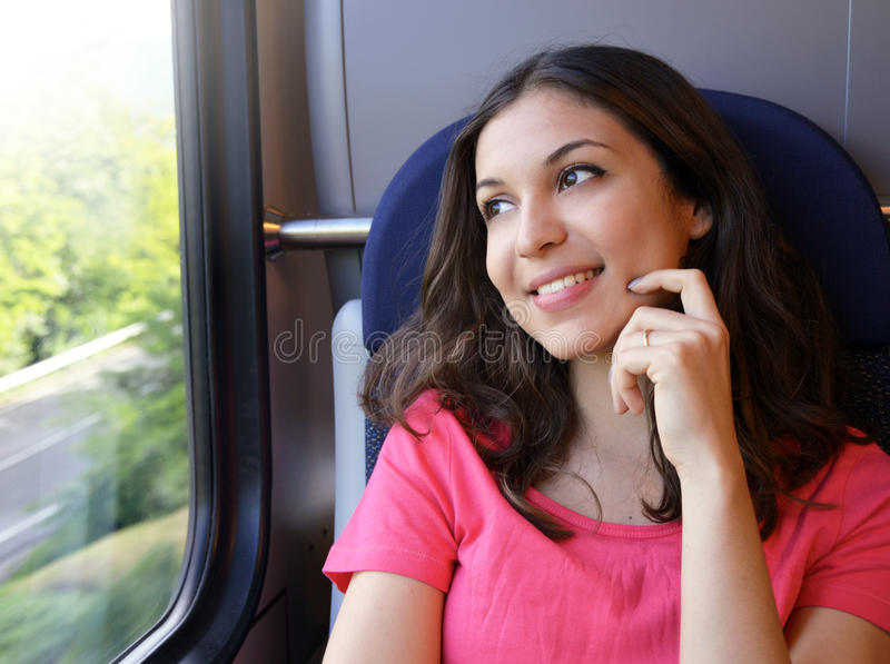 Young beautiful woman looking through the train window. Happy train passenger traveling sitting in a seat royalty free stock photography