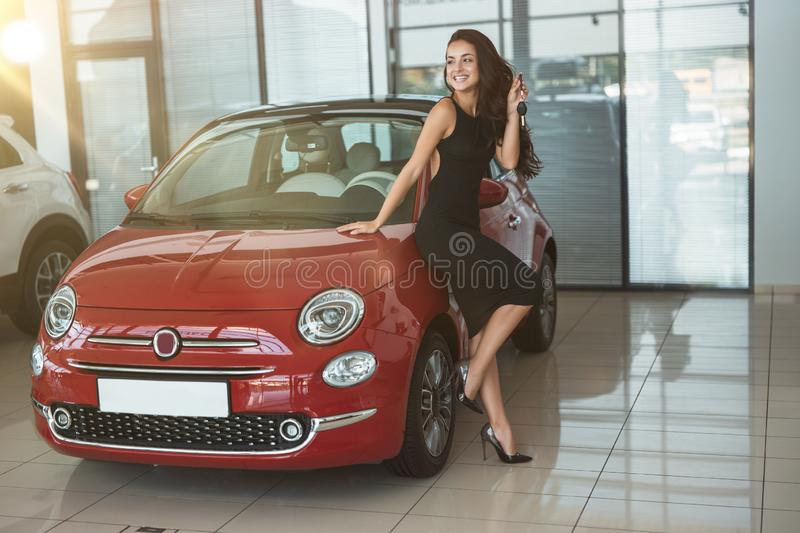 Young beautiful woman looks happy with car keys in her hand standing in dealership center near her brand new car royalty free stock photos
