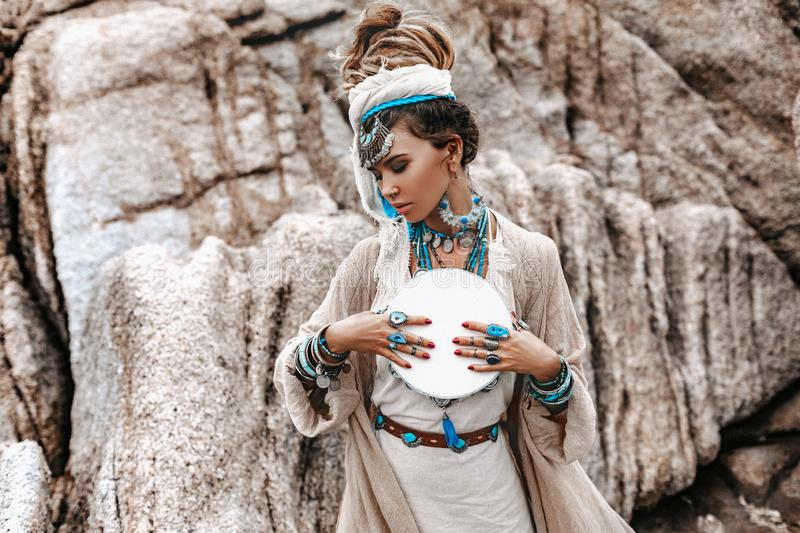 Young beautiful woman with lot of boho accessories with the drum outdoors royalty free stock photography