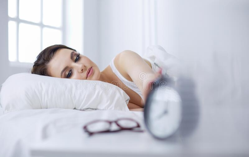 Young beautiful woman lying in bed. stock image