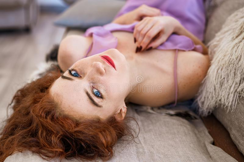 Young beautiful woman lying on bed, beautiful red hair, relaxation and relaxation concept royalty free stock image