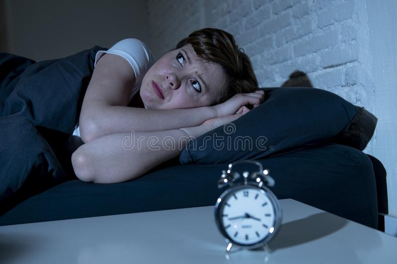 Young beautiful woman lying in bed late at night suffering from insomnia trying to sleep stock images
