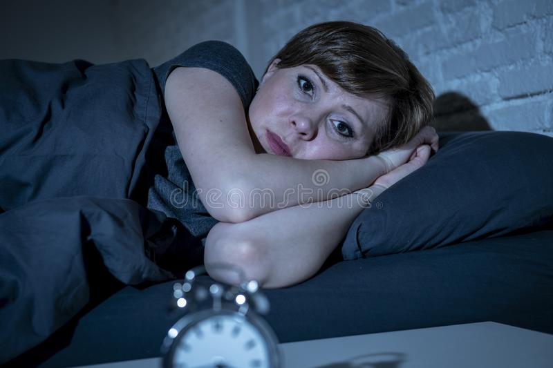 Young beautiful woman lying in bed late at night suffering from insomnia trying to sleep royalty free stock photos
