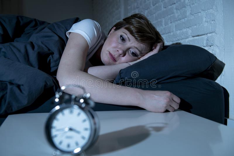 Young beautiful woman lying in bed late at night suffering from insomnia trying to sleep stock photo