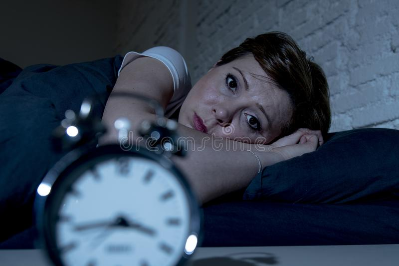 Young beautiful woman lying in bed late at night suffering from insomnia trying to sleep royalty free stock photography