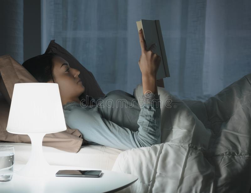Woman reading a book at night stock photo