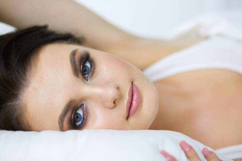 Young beautiful woman lying in bed. royalty free stock images