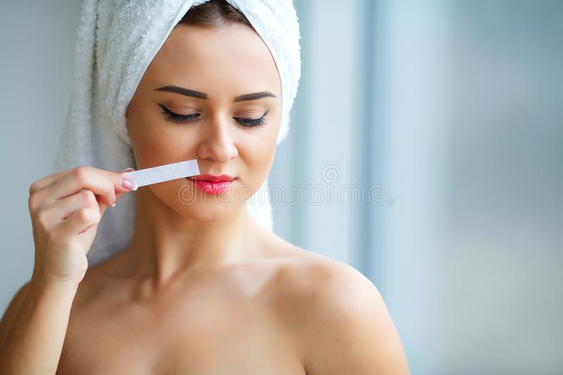 Young beautiful woman makes wax eyelids in her bathroom. Young beautiful woman makes wax eyelids in her bathroom stock image