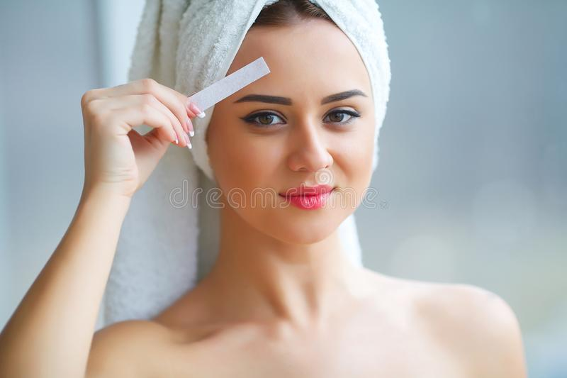 Young beautiful woman makes wax eyelids in her bathroom. Young beautiful woman makes wax eyelids in her bathroom royalty free stock photos