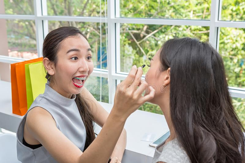 Young beautiful woman with Makeup Brush. Two friends making up in the cafe. asian girl. Friends are mascara brush royalty free stock photo