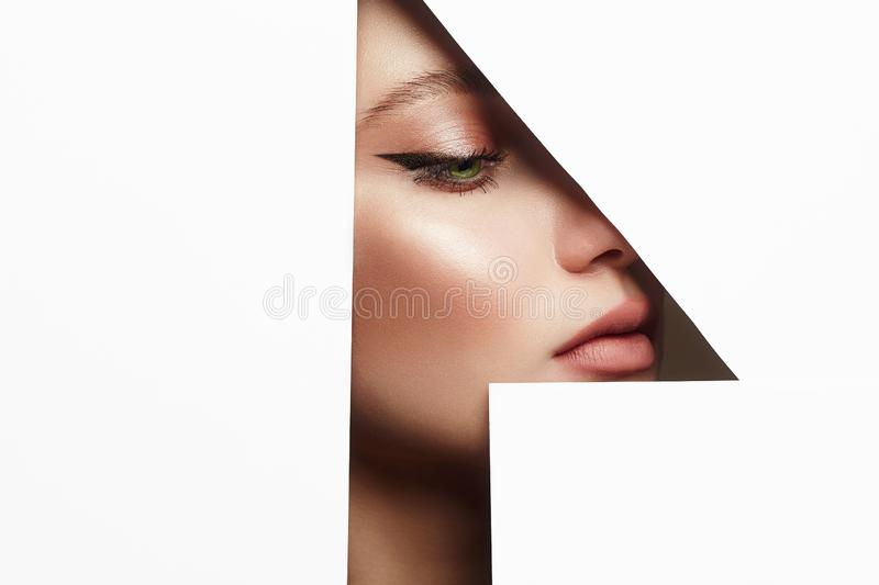 Arrows on the eyes. make-up artist concept. Young beautiful woman with makeup into paper hole. make-up artist concept. arrows on the eyes. number one stock photos