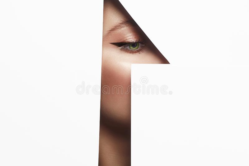Arrows on the eyes. make-up artist concept. Young beautiful woman with makeup into paper hole. make-up artist concept. arrows on the eyes. number one royalty free stock photo