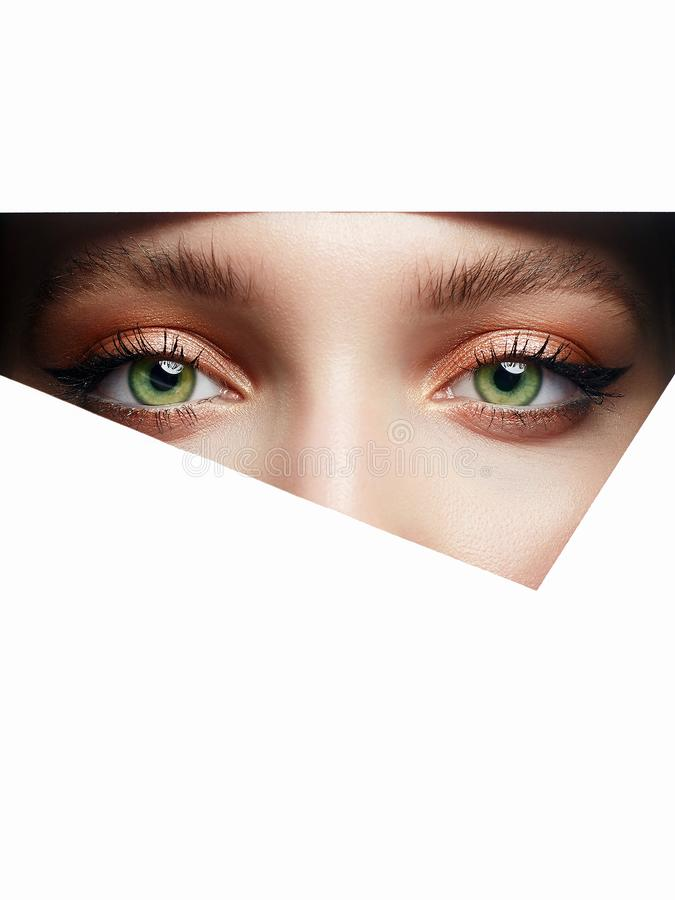 Young beautiful woman with makeup into paper hole. Make-up artist concept. arrows on the eyes. number one royalty free stock photos