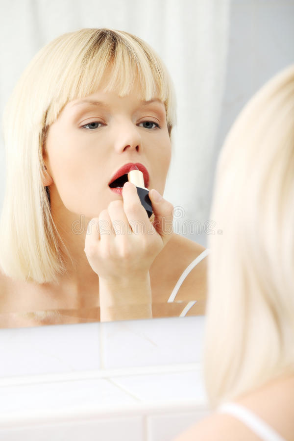 Young beautiful woman making make-up near mirror stock images
