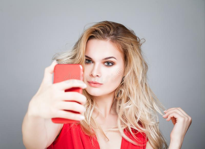 Young beautiful woman making selfie photo on smartphone. Fashion model girl with cell phone stock image
