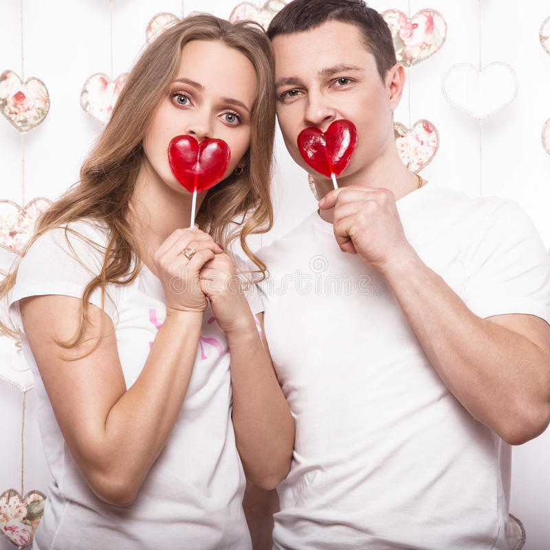 Young, beautiful woman and man in love on Valentine's Day with candy, Laughing Happy Lovers, showing different poses. Young, beautiful women and men in love on stock photos