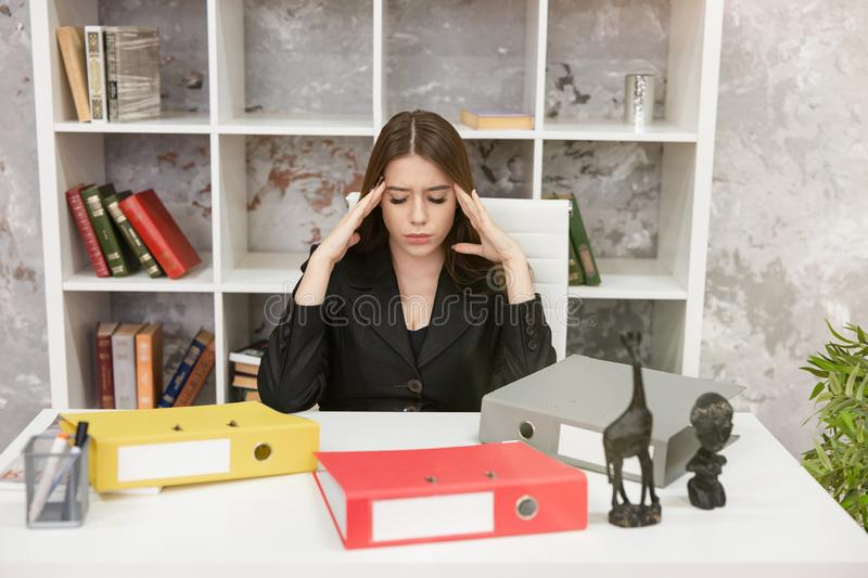 Young beautiful woman manager feeling stressed with folders on her table at her working place in office looking tired. Study royalty free stock photos