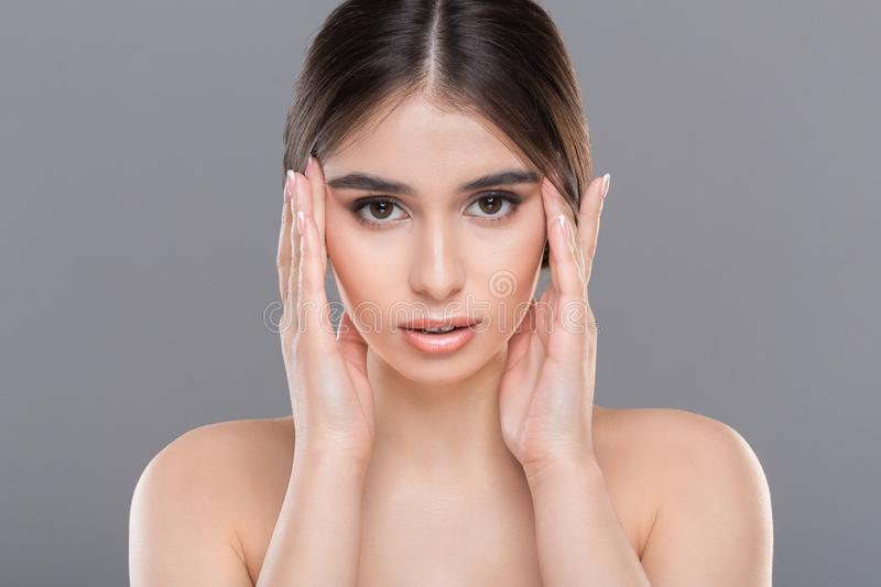 Young beautiful woman massaging her face closeup. Facial massage, wrinkles prevention. Young beautiful woman massaging her face royalty free stock images