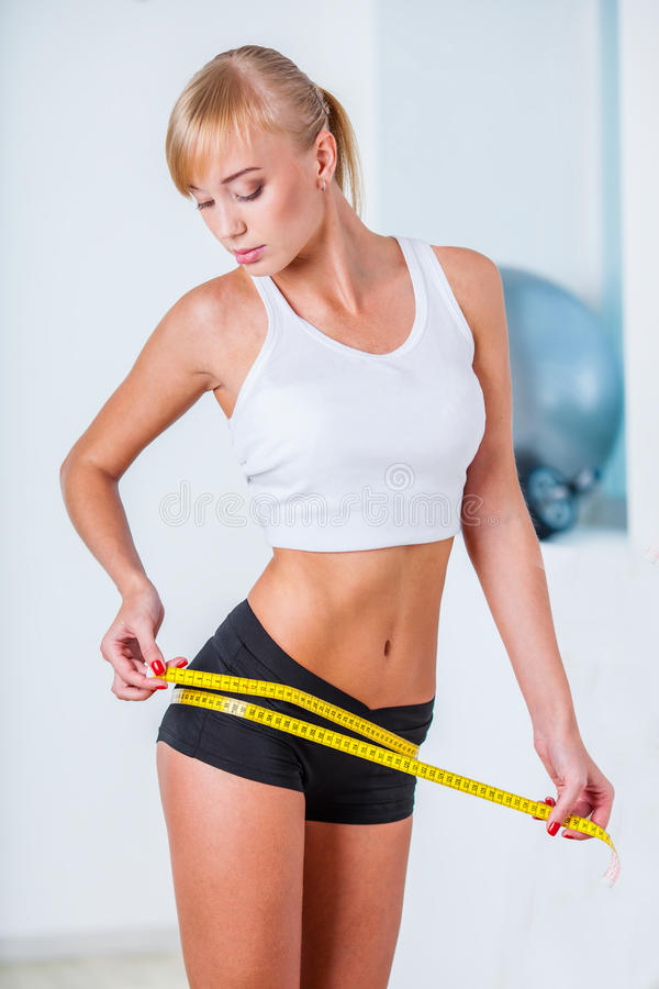 Young beautiful woman measuring her hips royalty free stock image