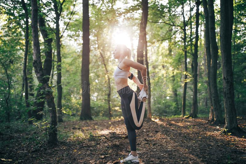 Young beautiful woman, morning, warm-up fitness outfit, royalty free stock image