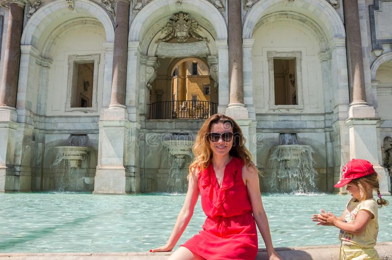 Young beautiful woman, mother and daughter on the Aqua Paola fountain in Rome, Italy royalty free stock photos