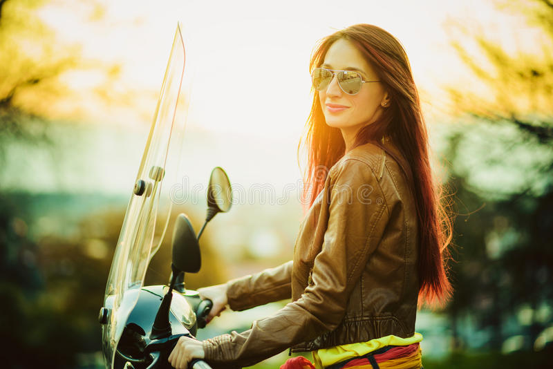 Young beautiful woman on motorcycle stock photo