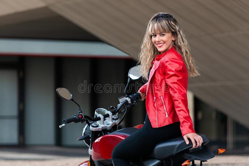 Young beautiful woman on motorcycle looking back stock photography