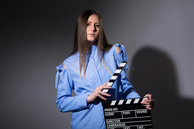 Young beautiful woman with movie cracker. Assistant director girl with long hair and striped shirt on a dark background stock photography