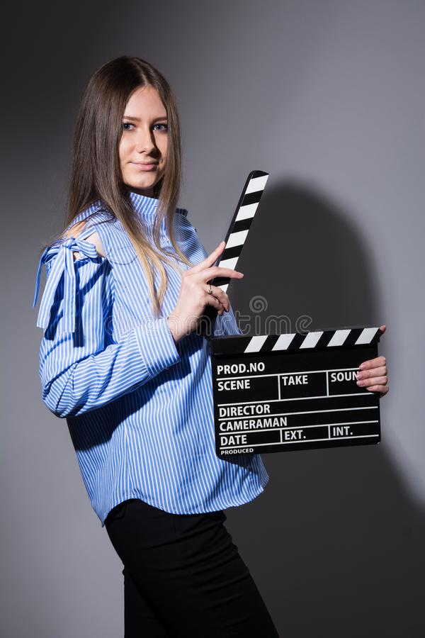 Young beautiful woman with movie cracker. Assistant director girl with long hair and striped shirt on a dark background stock image