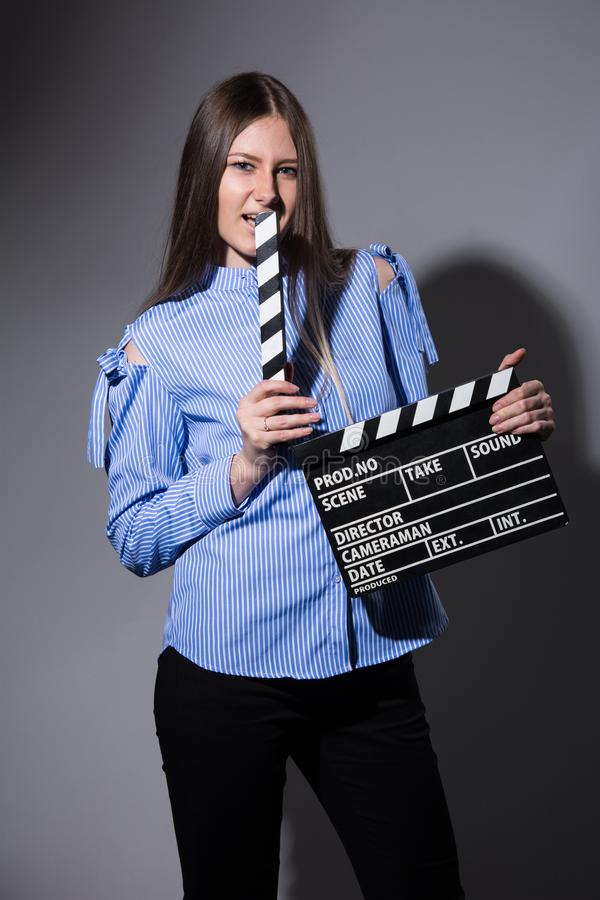 Young beautiful woman with movie cracker. Assistant director girl with long hair and striped shirt on a dark background stock photo