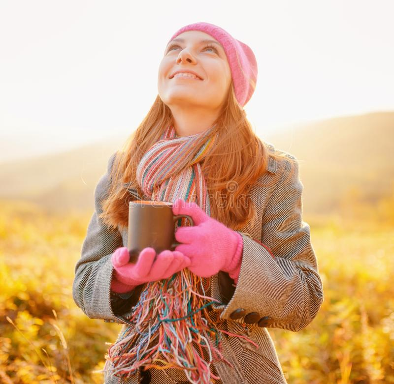 Young beautiful woman with mug in hand looking at the autumn sky stock photo