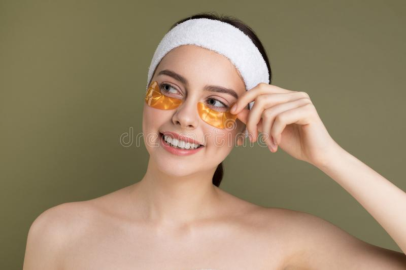 Young beautiful woman with natural make up removing gold patch from under her eye. Cosmetology and skin care.  on green stock photos