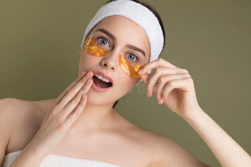 Young beautiful woman with natural make up removing gold patch from under her eye. Cosmetology and skin care.  on green stock photography