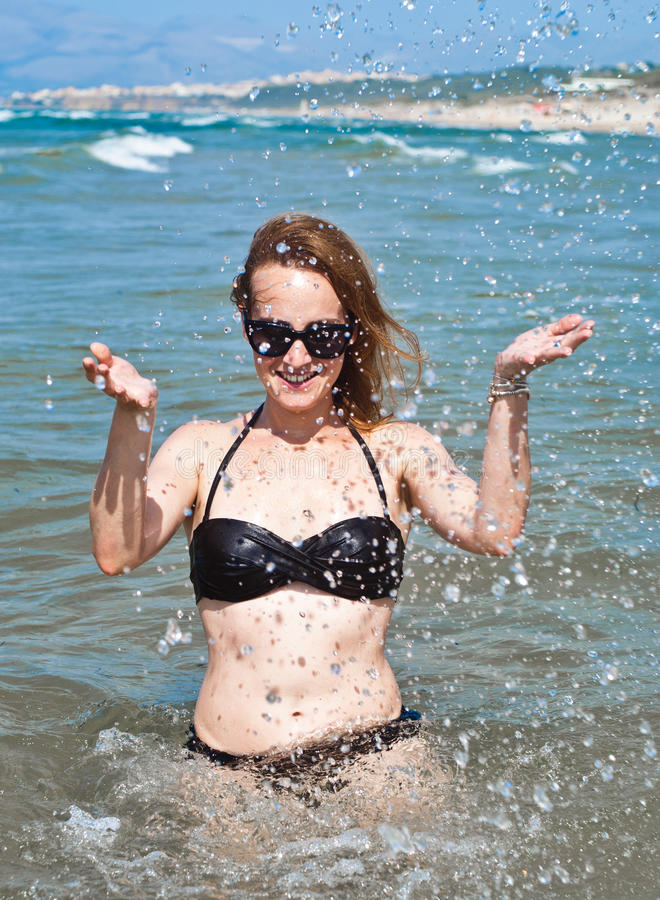 Young beautiful woman in ocean making water splashes stock images