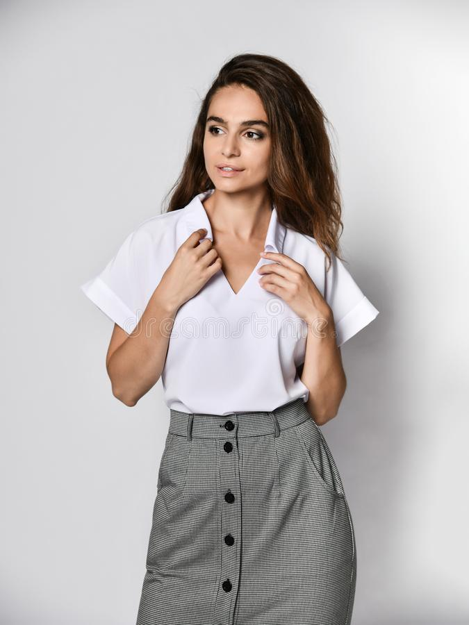 Beautiful woman office manager posing in a new casual white blouse and classic straight dark skirt. Young beautiful woman office manager posing in a new casual royalty free stock photo