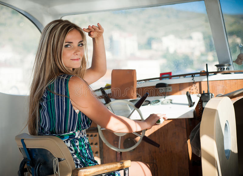 Young, beautiful woman operates the yacht stock images