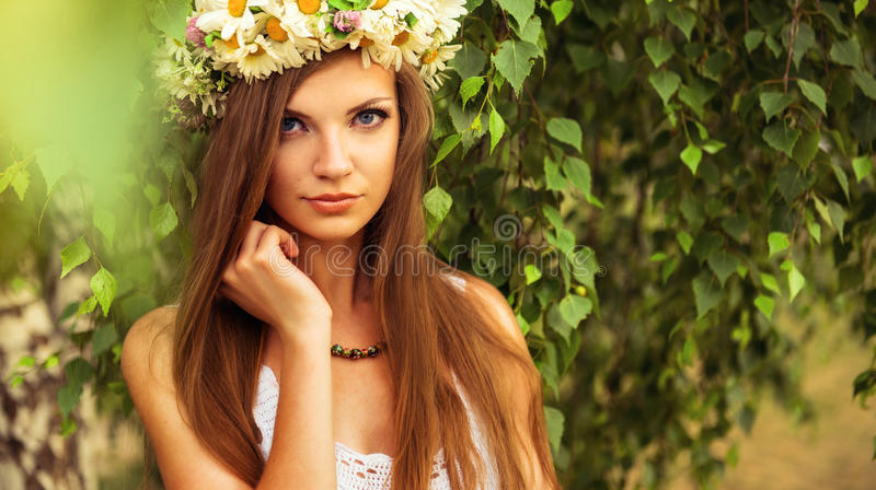 Young beautiful woman outdoor in a birchwood wearing wreth of daisy royalty free stock image