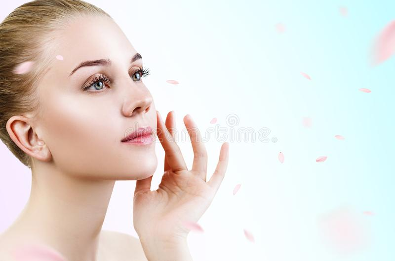Young woman over fresh blue background with swirl petals. stock photography