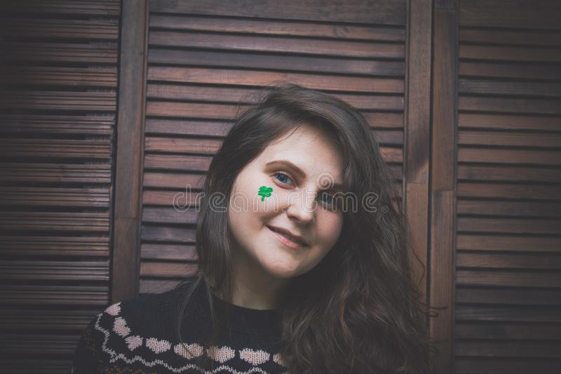 young beautiful woman with painted green clover on her cheek royalty free stock photo