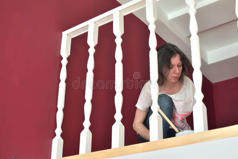 Young beautiful woman painting a ledge ballustrade white with a brush royalty free stock image