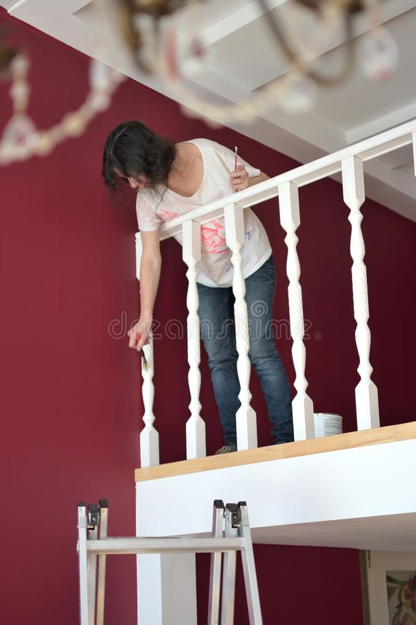 Young beautiful woman painting a ledge ballustrade white with a brush stock photos