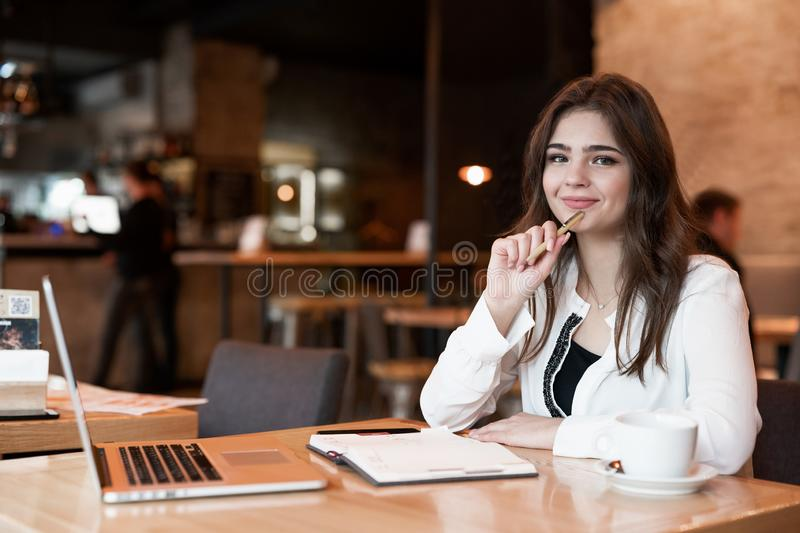 Young beautiful woman with pen in her hand taking notes to her planner using her laptop looks satisfied drinking hot coffee in stock images