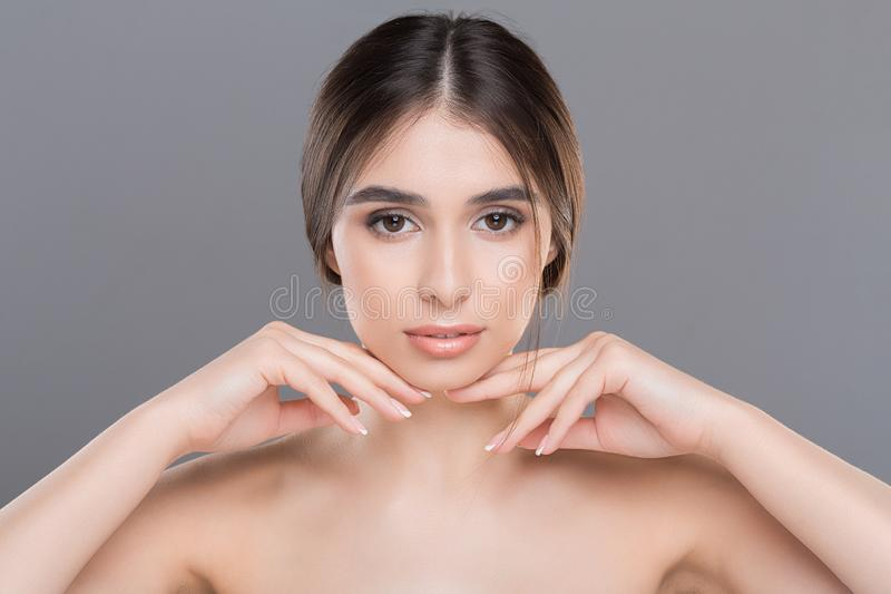 Young beautiful woman with perfect skin massaging her face. Prevention of double chin. Young beautiful woman with perfect skin massaging her face royalty free stock photography