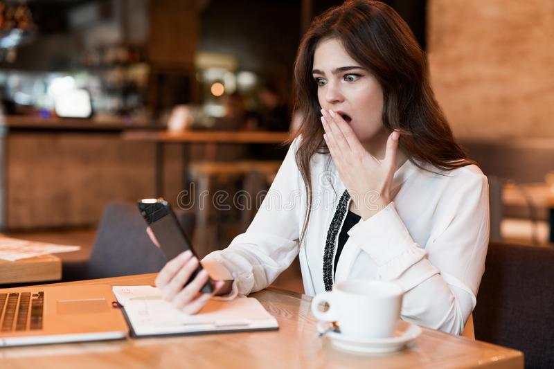 Young beautiful woman with phone in her hand working outside office in laptop looks shocked recieving bad news drinking hot coffee royalty free stock image