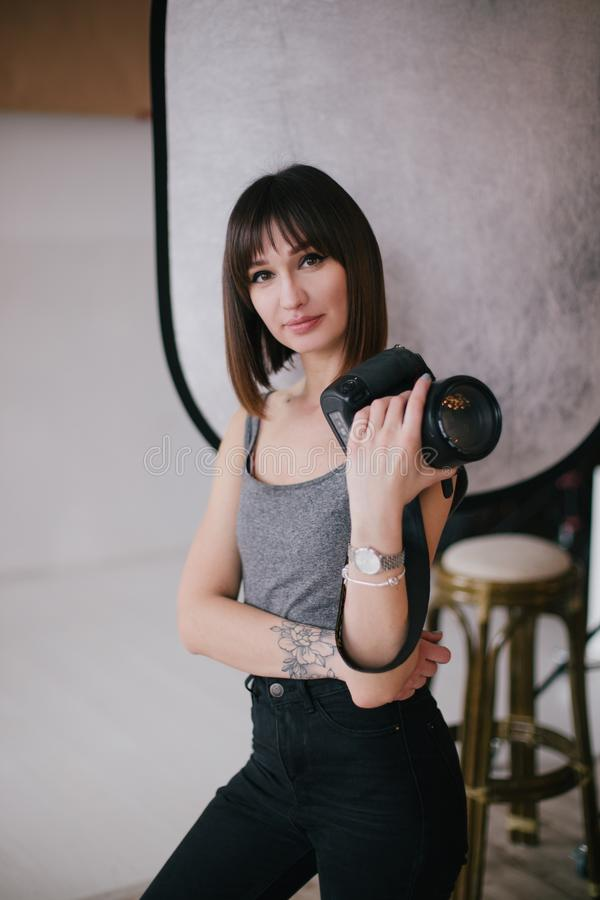 Young beautiful woman photographer with a professional photo camera in a studio royalty free stock photography