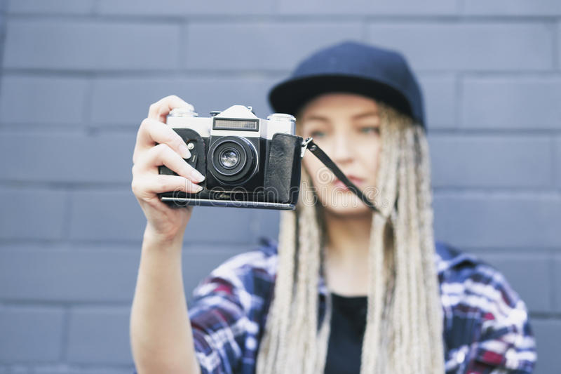 Young beautiful woman photographer is taking a photo stock photo