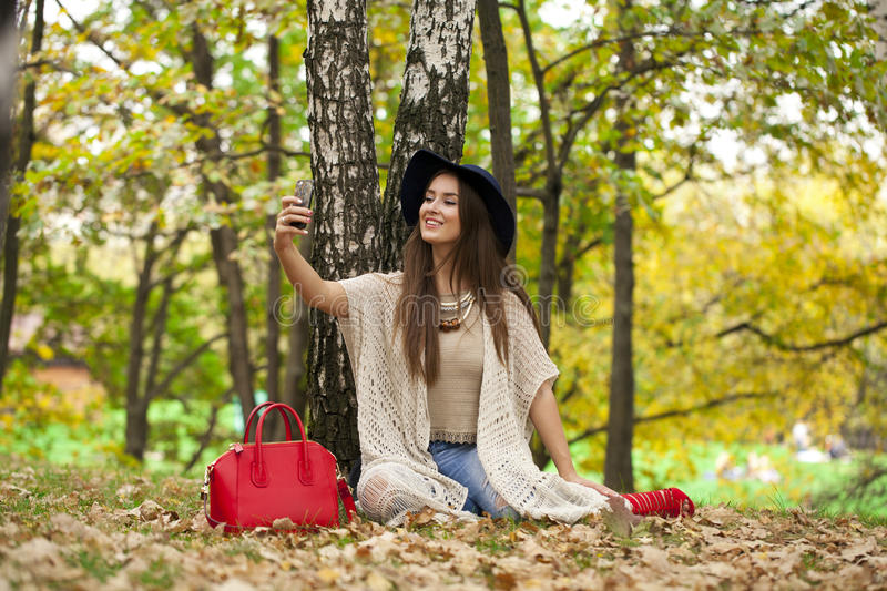 Young beautiful woman photographing themselves on a cell phone w royalty free stock images