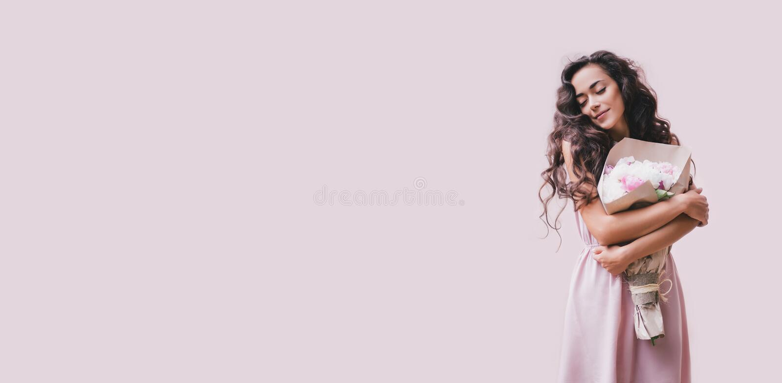 Young beautiful woman in a pink dress with a big bouquet of peonies on a pink background. Young beautiful woman with long curly hair in a pink dress with a big stock photography