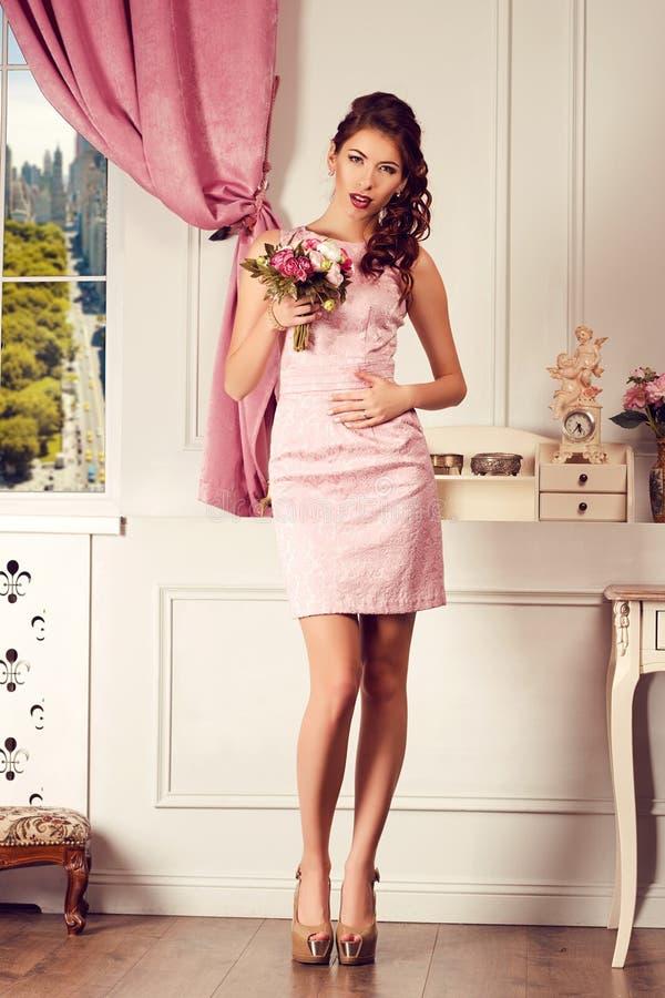 Young beautiful woman in pink dress. Fashion model shooting. stock photos
